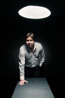 램프의 빛만 비추는 어두운 방에 서서 카메라를 바라보고 테이블 위에 손을 얹은 남자