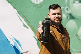 Man standing in front of graffiti wall with aerosol can in hand