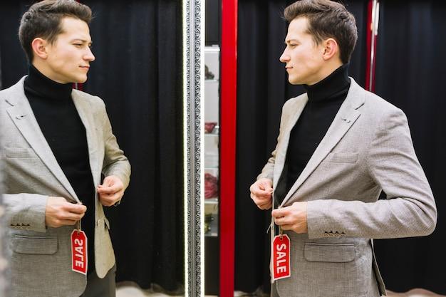 가게에서 거울을 시도하는 재킷 앞에 서있는 사람