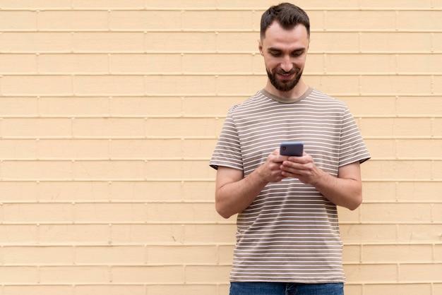Человек, стоящий перед стеной и использующий свой телефон