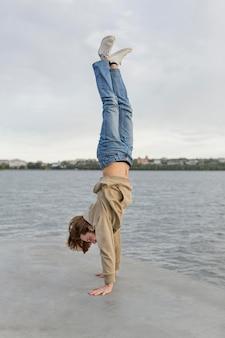 Человек стоит в руках рядом с озером