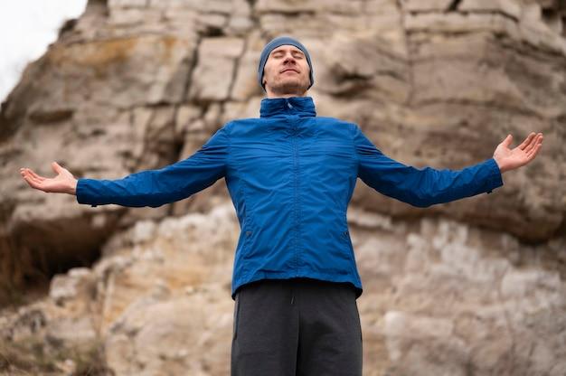 腕を開いて自然の中で立っている男