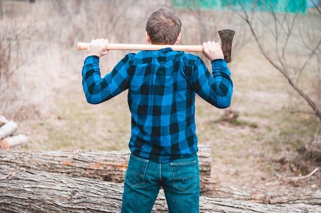 斧を持って森に立っている男