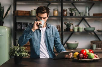 Man standing in the kitchen drinking coffee holding digital tablet