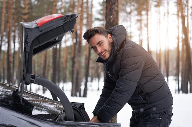 Человек, стоящий в зимнем лесу возле своей машины