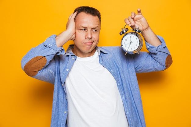 目覚まし時計を保持している黄色の壁の上に孤立して立っている男。