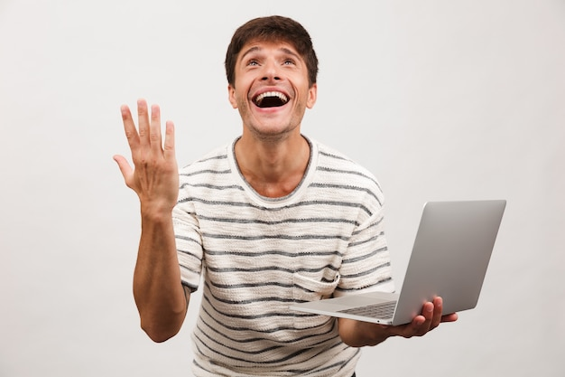 Man standing isolated on white using laptop computer.