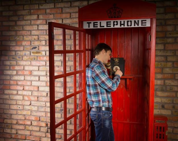 빈티지 다이얼 업 악기와 함께 빨간색 영국 전화 부스에서 전화를 걸고 서있는 남자