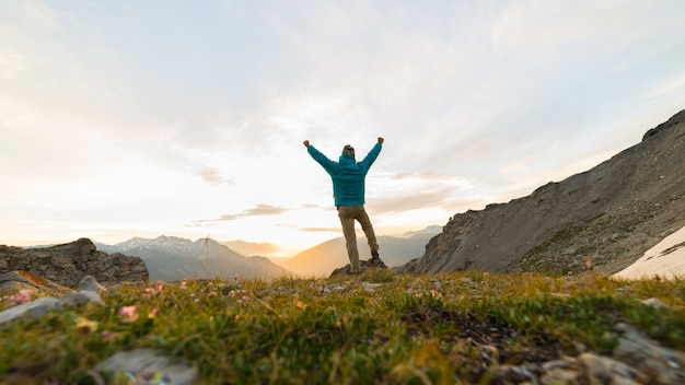 Man standing on mountain top outstretching arms, sunrise light colorful sky scenis landscape.