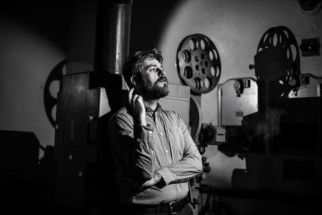 방 영사기에서 영화 영사기 근처에 서있는 남자