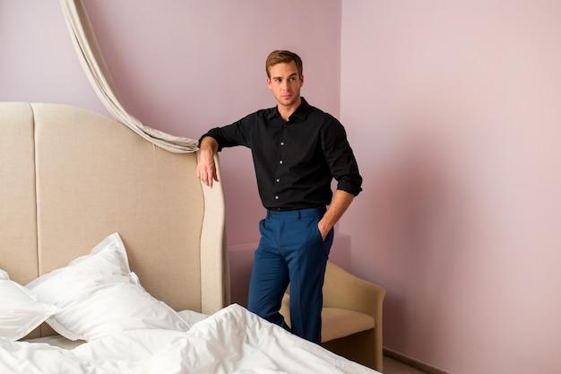 Человек, стоящий возле кровати.