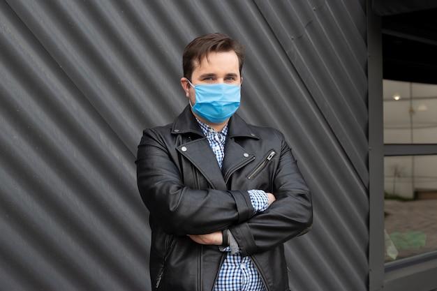 マスクを身に着けている黒い建物の近くに立っている人