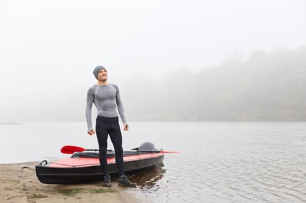 Человек, стоящий возле лодки на берегу реки и улыбающийся, одетый в спортивную одежду, смотрящий вдаль с улыбкой, наслаждающийся каякингом в озере, позирует с туманной рекой