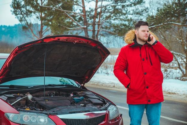Человек, стоящий возле разбитой машины на обочине дороги заснеженной зимней погодой. копировать пространство