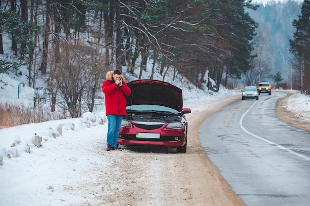 열린 후드가 있는 부서진 차 근처에 서 있는 남자가 도움을 요청합니다.