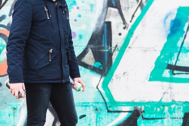 Man standing near graffiti wall