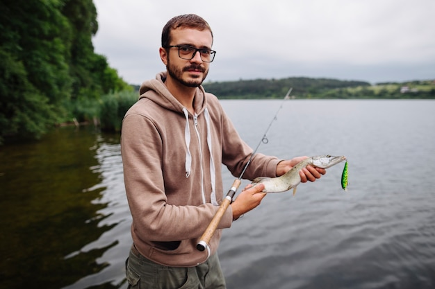 Man standing near the lake holding fish with hook