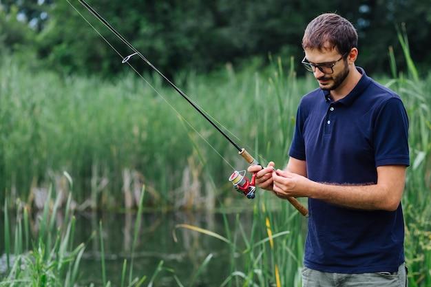 Человек, стоящий рядом с озером, завязывая приманку на удочку
