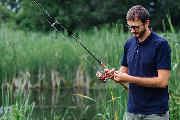 Man standing near lake tying fishing bait on rod