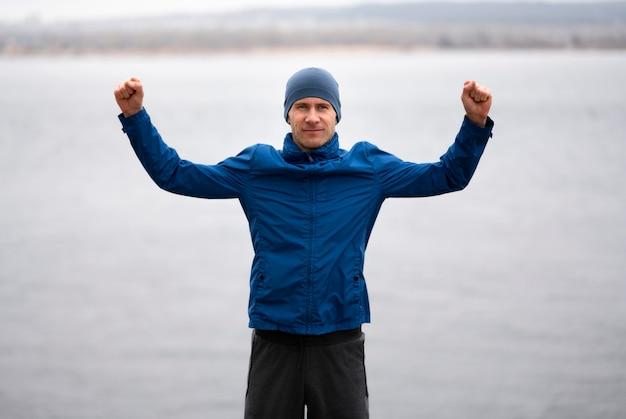 空中に腕を持って湖の近くに立っている男