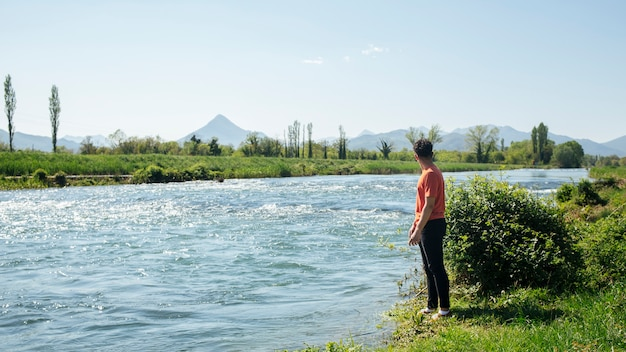 Man standing near natural flowing river