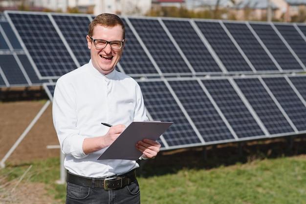 Человек, стоящий возле солнечных батарей