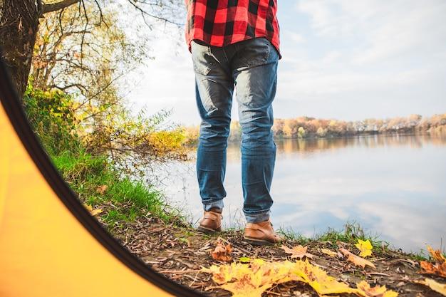 Человек, стоящий возле палатки, глядя на озеро осень осенний сезон