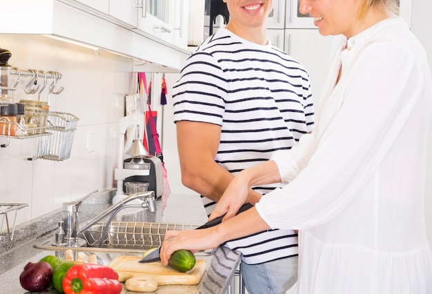 Man standing near the woman cutting vegetables with knife