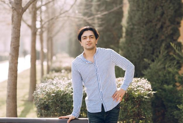 公園のベンチの隣に立っている男。高品質の写真