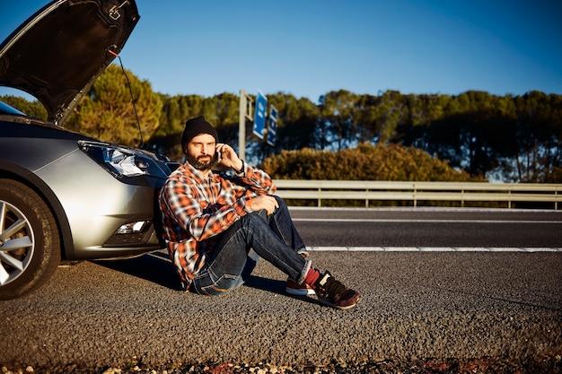 壊れた車の隣に立っている男性