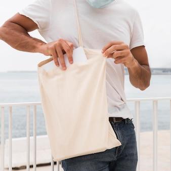 Человек, стоящий рядом с морем и держащий белую сумку, средний план