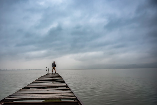 Man standing on a old wooden dock in stormy weather