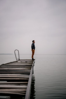 Man standing on a old wooden dock