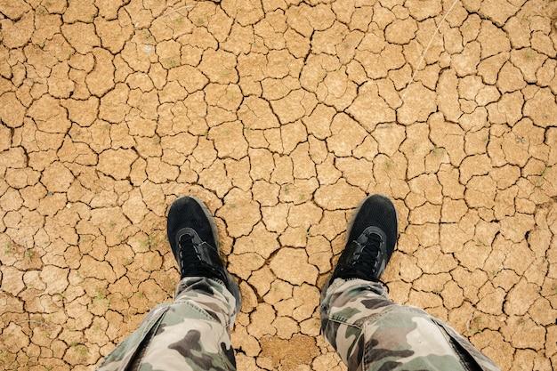 乾燥した割れた地球に立っている人。ひびの入った土の上に立っているスニーカーとミリタリーパンツの足、トップビュー。