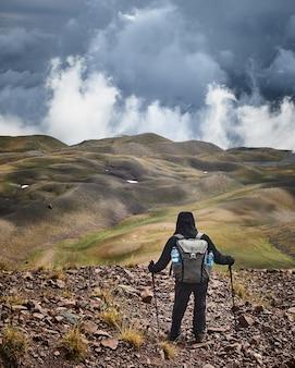 曇り空の景色を楽しみながら丘の上に立っている人