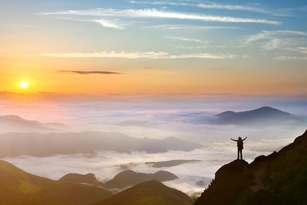 Человек, стоящий на горе с поднятыми вверх руками Premium Фотографии