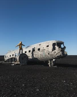 放棄された墜落した飛行機に立っている人