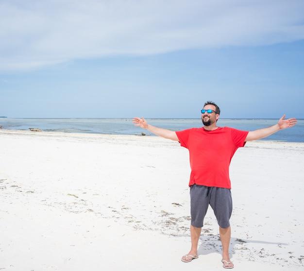 Человек, стоящий на пляже с белым песком