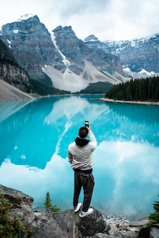낮 동안 모 레인 호수에 서있는 남자