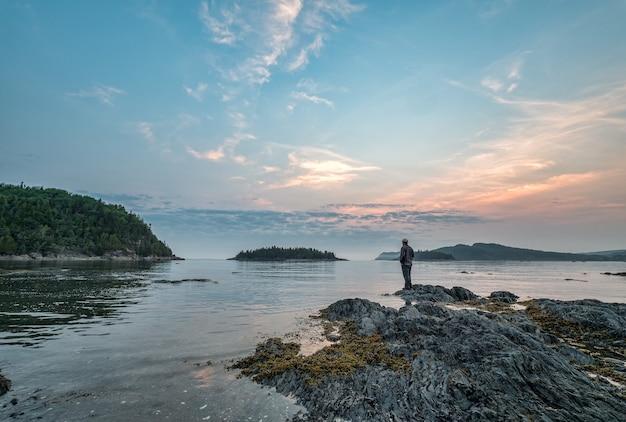 퀘벡에서 세인트 로렌스 강을 바라 보는 바위에 서있는 남자