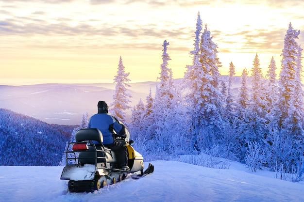 Человек, стоящий на заснеженной горе возле снегохода, наслаждаясь видом зимнего леса на закате. концепция зимних путешествий, спорта, деятельности.