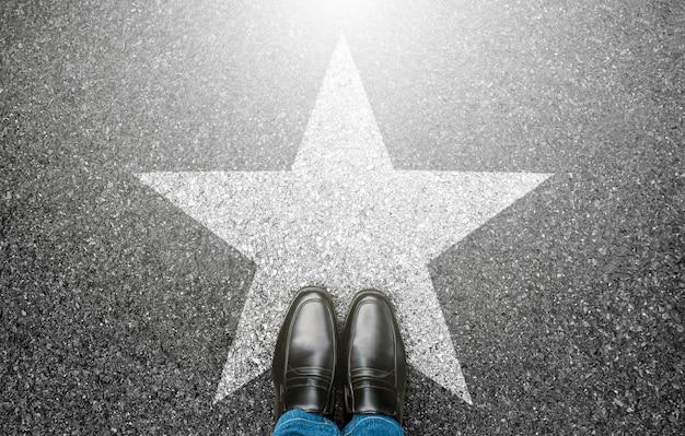 Человек, стоящий на улице, вид сверху, селфи ног в черных туфлях и символ белой звезды