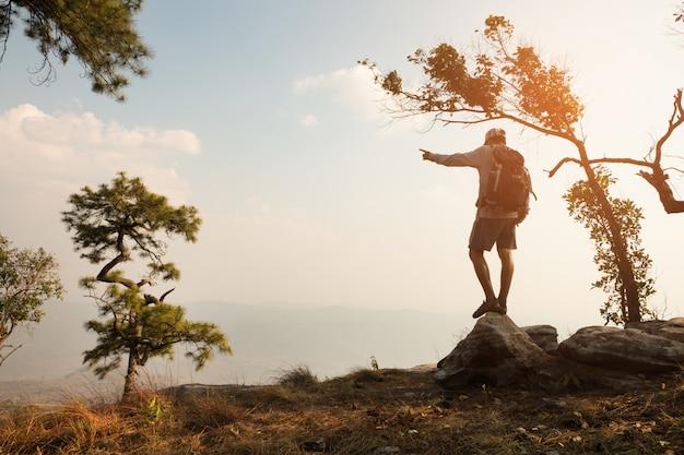 Человек, стоящий на скале в долине и горах.