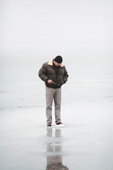 Man standing on the frozen lake fishing