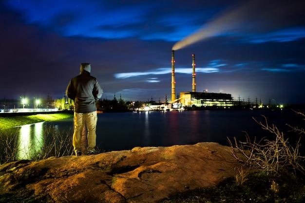 강둑에 서있는 남자는 밤에 발전소를 본다.