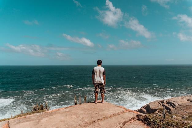 日光と青い空の下で緑と海に囲まれた岩の上に立っている男