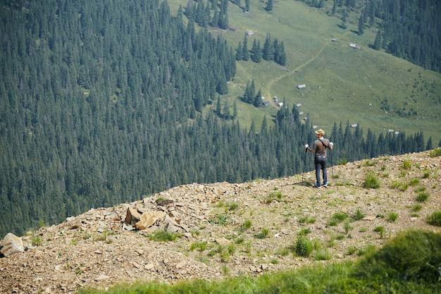 산과 숲을 볼 수있는 바위 꼭대기에 서있는 남자
