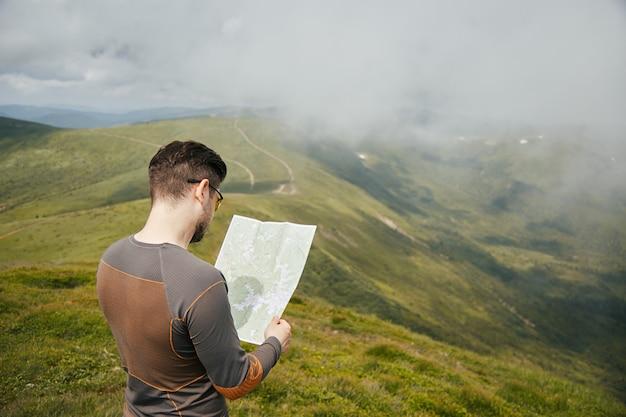 지도와 함께 maountain 위에 서있는 남자