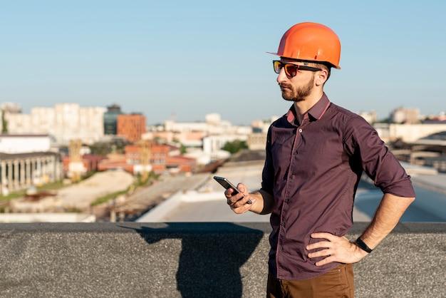 전화 손에 건물 위에 서있는 남자