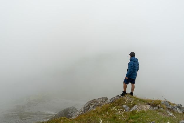 霧のある風景を眺める山の頂上に立っている男